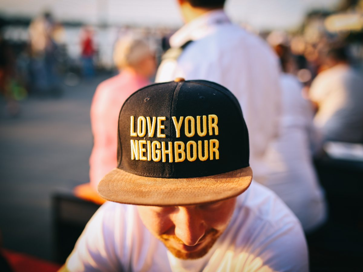 "Man in baseball cap inscribed ""Love Your Neighbor"