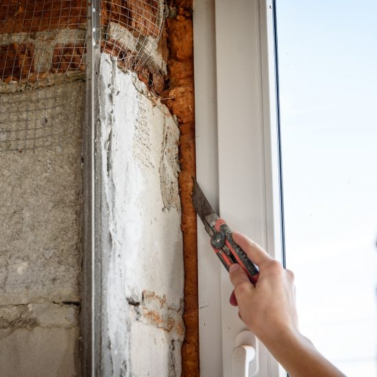 Man's hand scraping wall interior with a putty knife.