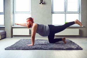 A smiling, overweight, bearded man in exercise clothes does yoga on a rug to enrich coronavirus self-isolation time.
