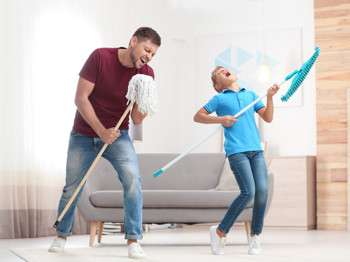 Dad and son having fun playing air guitar with cleaning mops during stay-home lockdown