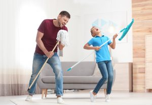 Dad and son having fun playing air guitar with cleaning mops